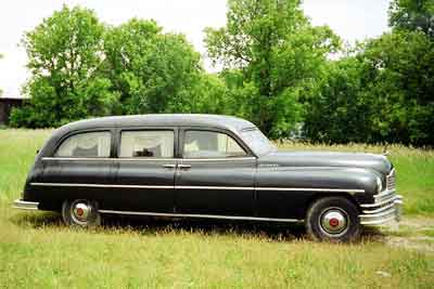 Full profile photo of a 1949 Henney Packard hearse relaxing in a farmer's field.