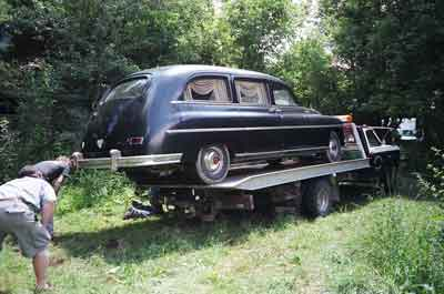 Image of a long 1949 Henney Packard hearse just barely fitting on a flatbed trailer.
