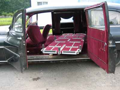 Image of 1949 Henney Packard with driver's side suicide doors open to show lateral access to sliding casket bed.